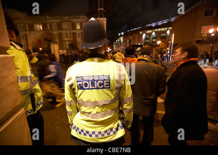 metropolitan police officer on duty outside chelsea football stadium at night London England Uk United Kingdom - Stock Photo