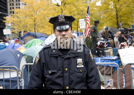Serious looking NYPD officer at the Occupy Wall Street encampment in downtown Manhattan at Zuccotti Park, New York - Stock Photo