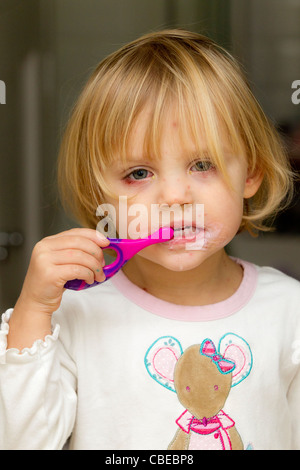 Sad-looking little girl with chicken pox cleaning her teeth. - Stock Photo