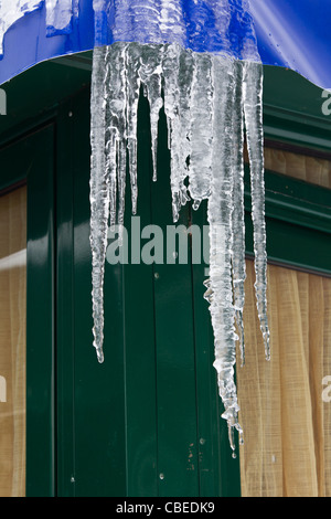 melting icicles and water drops from a metal building with trapulin roof - Stock Photo