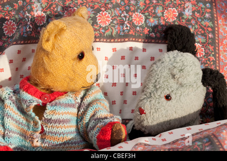 old teddybear and puppet (Sweep) in bed - Stock Photo