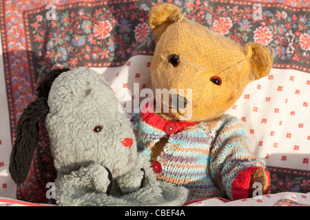 old toys, teddybear and puppet (Sweep) in bed - Stock Photo