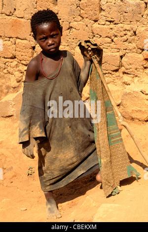 Kala, Tanzania. Girl in ragged clothes holding a stick; Lake Tanganyika. - Stock Photo