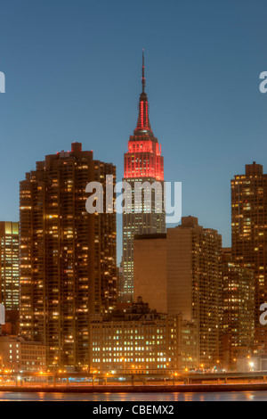 The Empire State Building, lit in red for World Aids Day, and other buildings on the east side at twilight in New - Stock Photo