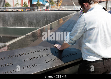 A visitor reads the names at the National September 11 Memorial in New York City. - Stock Photo