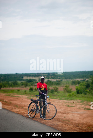 Man With A Bike Wearing A Tee Shirt With The National Flag Colors, Angola - Stock Photo