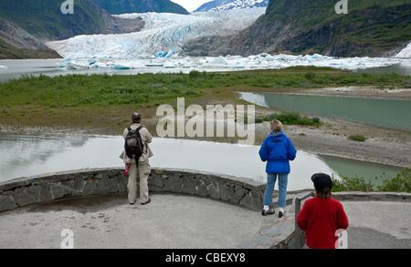 Family contemplating the Mendenhall glacier. Juneau. Alaska. USA - Stock Photo