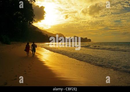 Couple walking along the beach at Beau Vallon bay, Mahe Island, Seychelles at sunset - Stock Photo