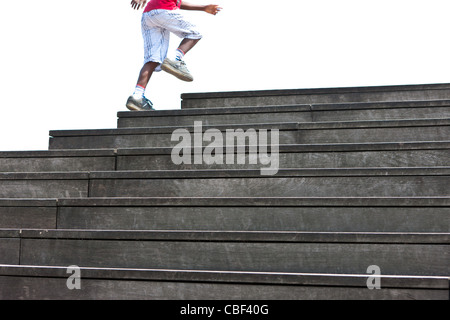 A boy runs up the steps to the French National Libary, Mitterand site, in Bercy, Paris, France. - Stock Photo