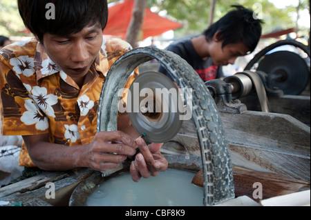 Men grinding jade on a machine to their final shape, Bogyoke Aung San Jade Market, Mandalay, Myanmar (Burma). - Stock Photo