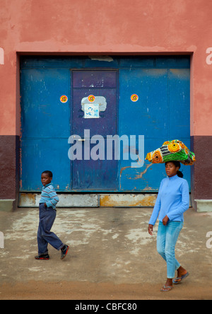 Boy And Woman Carrying A Load On Her Head In Lubango Streets, Angola - Stock Photo
