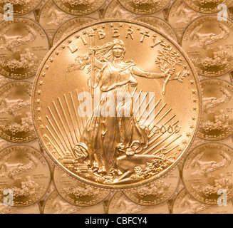 Gold Eagle one ounce coins in a patterns and stacked on each row with a single Liberty coin on the top