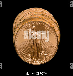 Gold Eagle one ounce coins in a stack and isolated against black