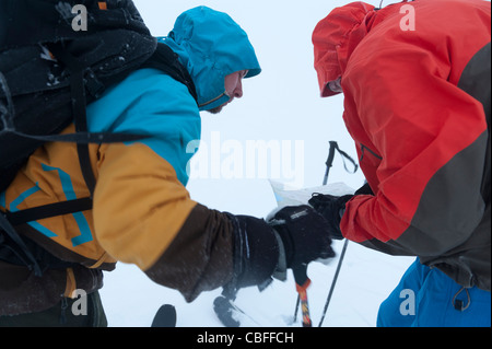 Two men orienteering in foggy conditions while ski-touring in Tamok, north Norway - Stock Photo