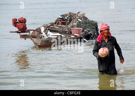 Traditional fisherman with his catch of fish and his fishing boat in Patong, Phuket, Thailand - Stock Photo