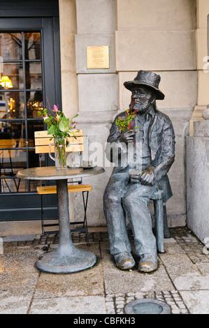 Statue of Polish director Piotr Skrzynecki sitting outside a cafe, Krakow - Stock Photo