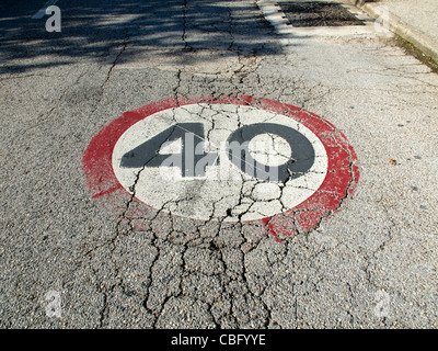 40 speed limit traffic sign painted on an old road - Stock Photo