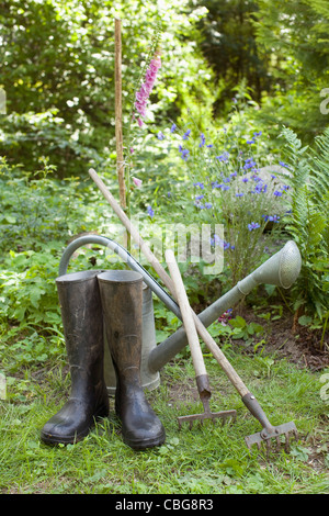 Gardening tools and a pair of rubber boots, outdoors - Stock Photo