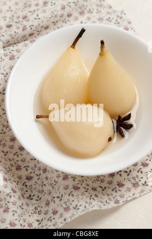 Poached pears in light syrup with spices on a flowered napkin. - Stock Photo