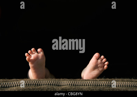 The soles of a baby's feet lying on a pillow - Stock Photo