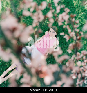 A girl lying on grass looking up at cherry tree blossoms - Stock Photo