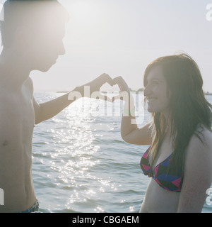 A young couple making a heart sign with their hands - Stock Photo