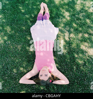A girl lying in grass with hands behind head, upside down view - Stock Photo