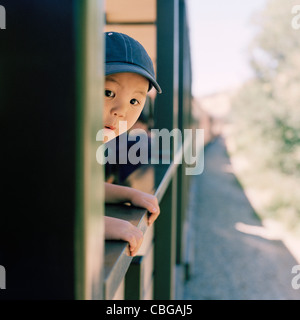 An excited boy leaning out of a train window - Stock Photo