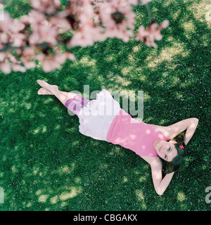 A teenage girl lying in grass with hands behind head, looking up - Stock Photo