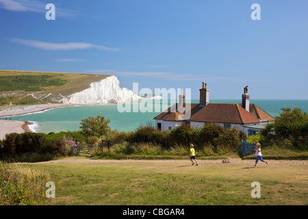 Children running near Cuckmere beach, Seven Sisters white chalk cliffs, East Sussex, England, UK, United Kingdom, - Stock Photo