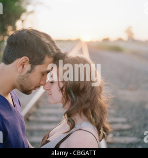 A young couple touching foreheads near railroad track - Stock Photo
