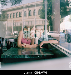 A young teenage couple sharing a milkshake at a diner, viewed through window - Stock Photo