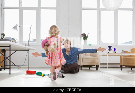 A young girl running towards her father sitting on the floor - Stock Photo