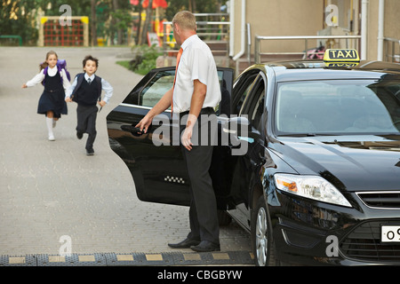 Two children in school uniforms running towards black cab - Stock Photo