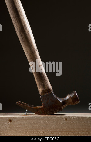 A hammer removing a nail from a wood beam - Stock Photo