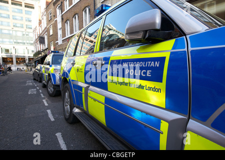 metropolitan police vehicles with battenburg chequered livery parked in reserved onstreet bays london england uk - Stock Photo