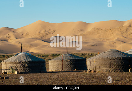nomadic gers under the sand dunes of Khongoryn Els at sunset in the Gobi Desert of Mongolia - Stock Photo