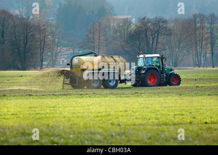 Liquid Cow Manure being sprayed on field, Chiemgau Upper Bavaria Germany - Stock Photo