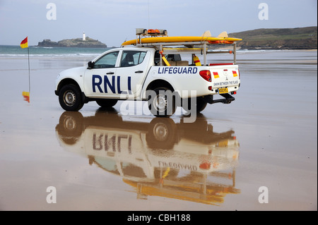 An RNLI lifeguard's rescue truck with surfboard on a sandy beach. Rescue vehicles with sand and sea. - Stock Photo