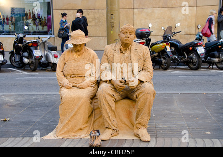 Spain, Catalunya, Barcelona. Popular downtown pedestrian street, La Rambla. Typical street mime with tip jar along - Stock Photo