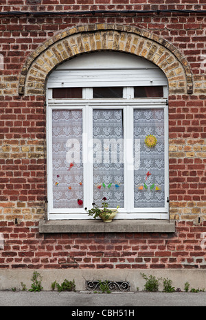 Window in old red brick wall with lace curtains Bergues France - Stock Photo