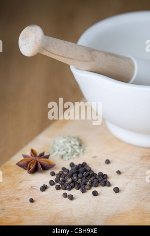 a porcelain pestle and mortar with black peppercorns, star anise and fennel seeds on a wooden chopping board - Stock Photo