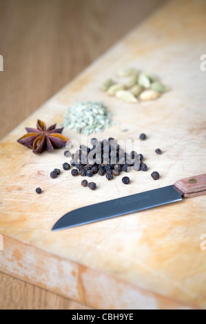 black peppercorns, star anise, fennel seeds and cardamom pods on a wooden chopping board - Stock Photo
