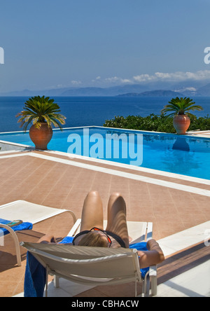 Woman relaxing on sun lounger with luxury infinity pool and coastal sea view behind - Stock Photo