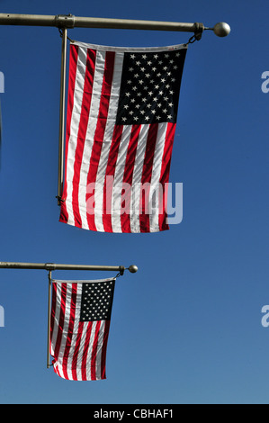Two American Flags against blue sky. - Stock Photo