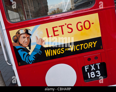 Historic 1940's restored traditional UK red double decker bus, with WW2 poster and slogan ' Wings for Victory' - Stock Photo