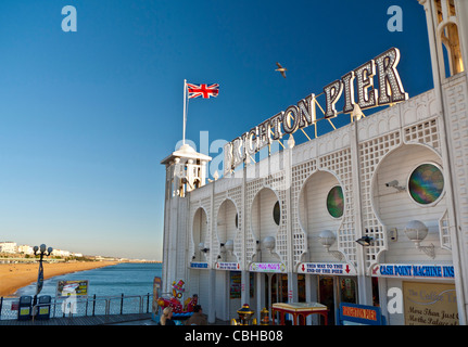 Brighton Pier with Union Jack flag flying and sunlit beach behind Brighton West Sussex England UK - Stock Photo