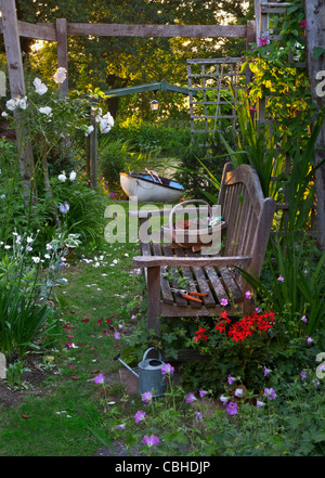 Wooden garden bench under perigola in floral garden with traditional trug gardening tools rowing boat and river - Stock Photo