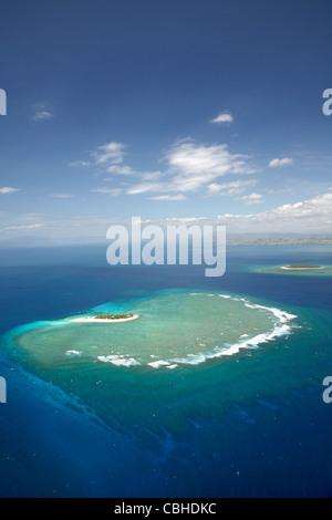 Surf on reef off Namotu Island, and Tavarua Island in distance, Mamanuca Islands, Fiji, South Pacific - aerial - Stock Photo