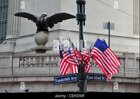 The symbol of America the bold Eagle and Americans flags hanged outside the Grand central station of Manhattan New - Stock Photo